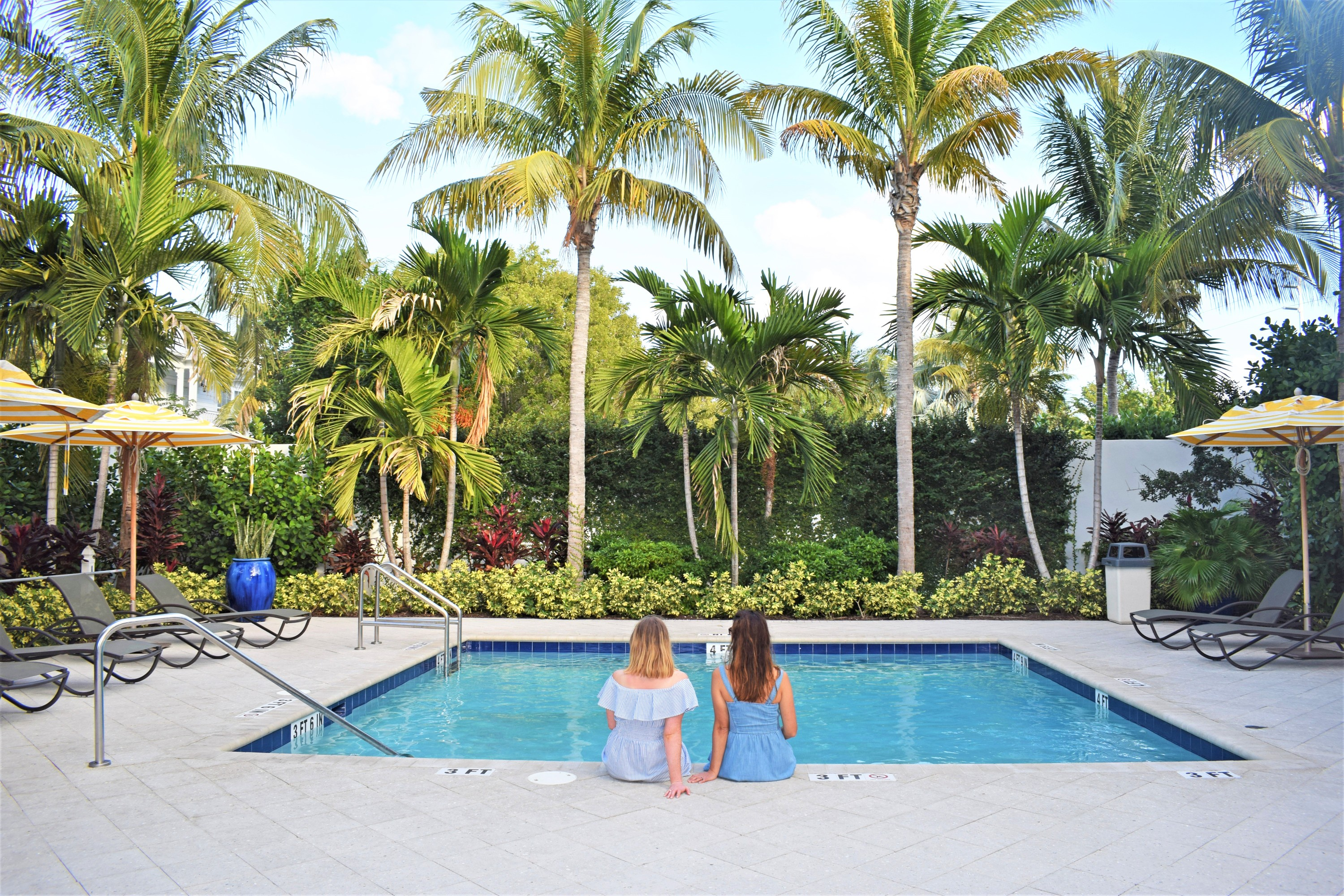 Two young women sitting by the edge of a pool surrounded by palm trees in the Florida Keys