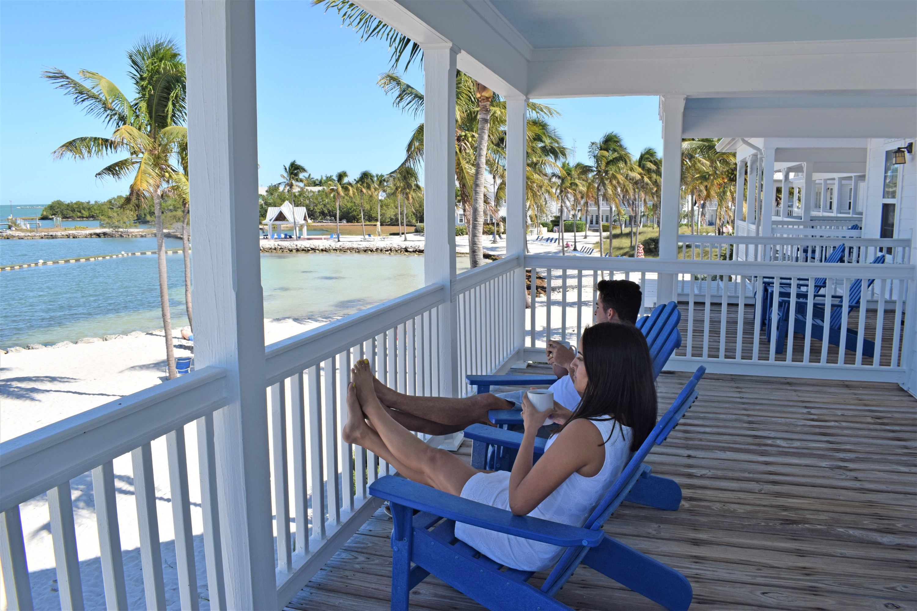 Couple relaxing on balcony overlooking Gulf of Mexico at Tranquility Bay