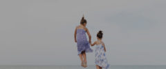 Two girls jumping on a sandy beach in the Florida Keys