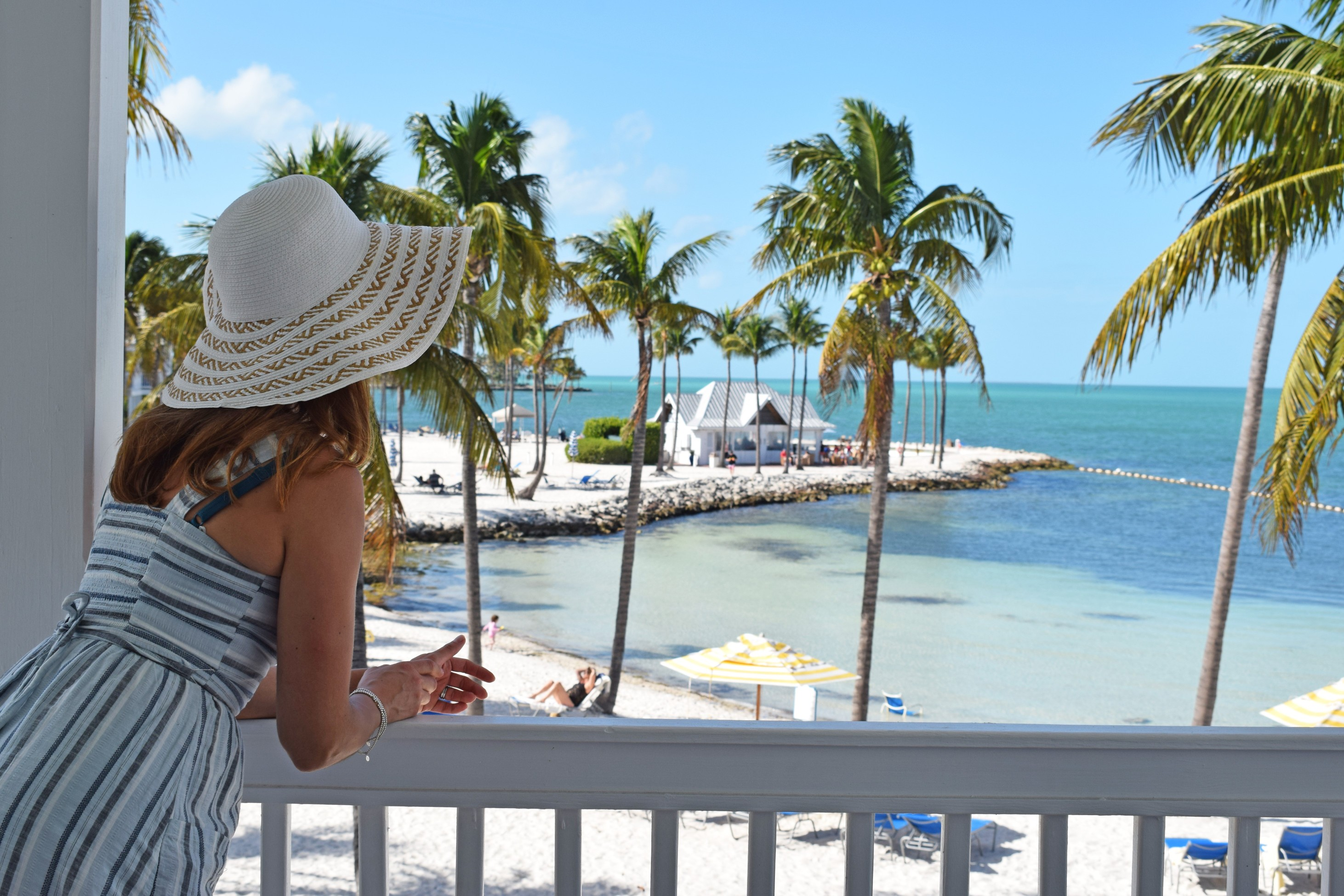 Woman on balcony overlooking private beach in the Florida Keys